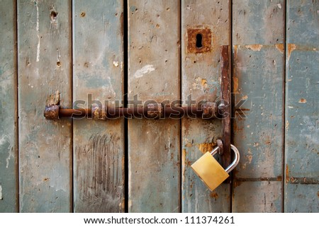 Weathered old door with lock, bolt and keyhole, landscape orientation. - stock photo