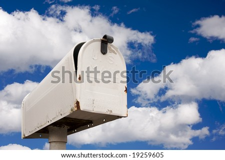 Weathered Old Mailbox Against Blue Sky and Clouds - stock photo