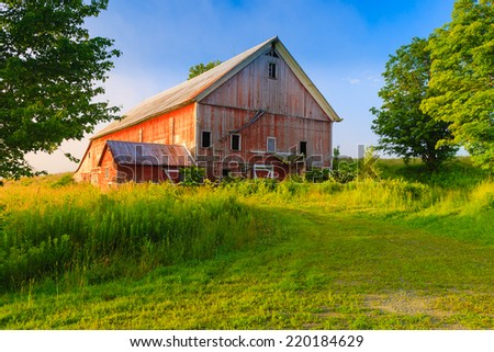 Weathered old red barn in a rural setting, Stowe, Vermont, USA - stock photo