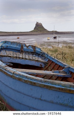 Weathered old rowing boat in foreground. Holy Island or Lindesfarne in the background.