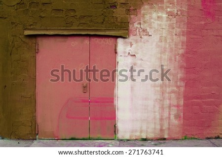 weathered painted wall with metal door - stock photo
