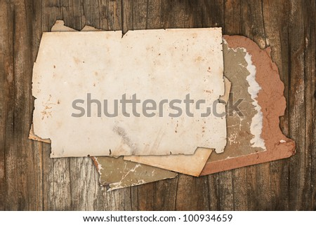 Weathered paper and old cardboard on a wooden background - stock photo