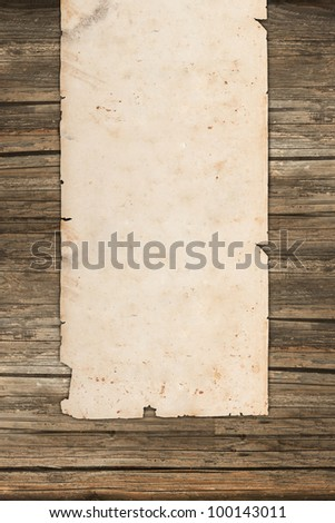 Weathered paper roll on vintage wooden background - stock photo