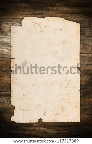 Weathered paper sheet on a dark wooden background - stock photo