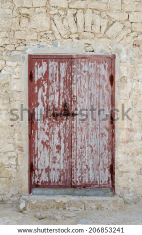 Weathered red door in traditional moroccan house - stock photo