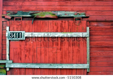 Weathered Sliding Barn Door With Address, Hanging On Old Red Barn.