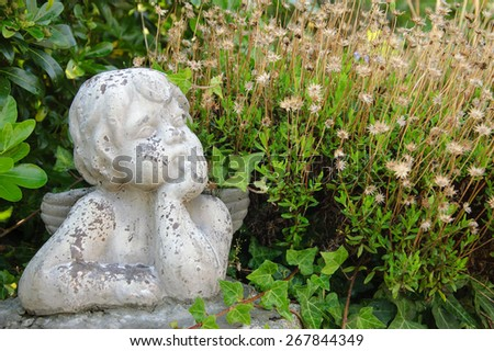 Weathered statue of an infant angel in overgrown garden.  - stock photo