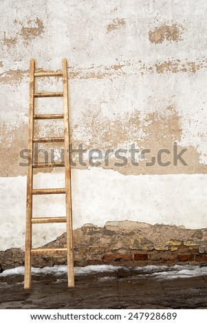 weathered stucco brick wall with wooden ladder background - stock photo