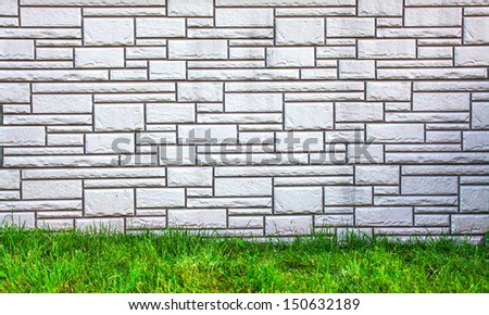 Weathered texture of stained old dark brick wall background, grungy rusty blocks of stone-work technology, white horizontal architecture with bright green grass outdoor in the park