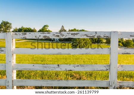 Weathered white wooden horse fence on country site. - stock photo