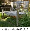 Weathered wood bench n green garden - stock photo