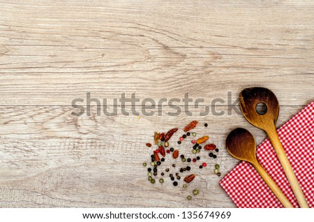 Weathered wood with cooking spoon and checkered napkin - stock photo