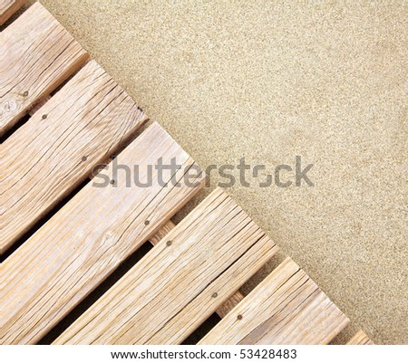 Weathered wooden boardwalk on  sand - stock photo