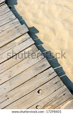 Weathered wooden boardwalk on sand dune at Couronian lagoon - stock photo