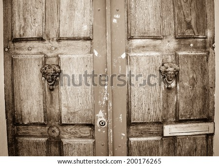Weathered wooden door with decorative handles - in shape of human head with wreath on it (like Roman patrician). Paris, France. Aged photo. Sepia. - stock photo
