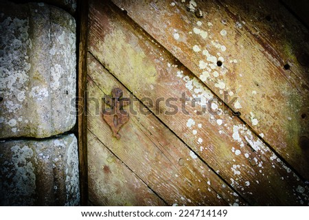 Weathered wooden door with rusty decorative key hole. Old farmhouse in Brittany, France. Aged photo. Shadowed angles. - stock photo