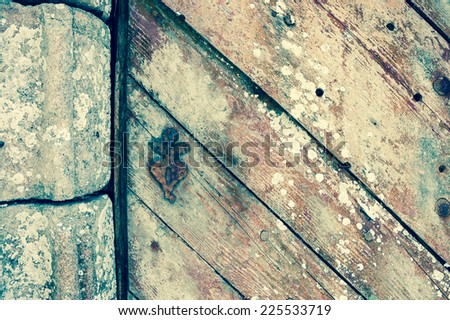 Weathered wooden door with rusty decorative key hole. Old farmhouse in Brittany, France. Aged photo.  - stock photo