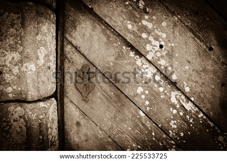 Weathered wooden door with rusty decorative key hole. Old farmhouse in Brittany, France. Aged photo. Sepia. Shadowed angles. - stock photo