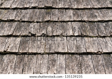 Weathered wooden shake shingles on a pitched roof show detail. - stock photo