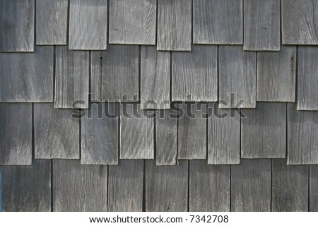 Weathered wooden shingles from the siding of a beach house - stock photo