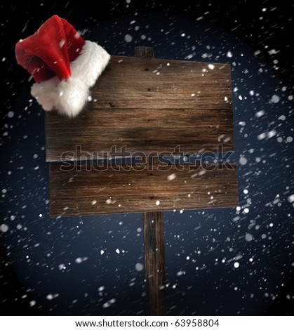 Weathered wooden sign with Santa hat on snowy background - stock photo