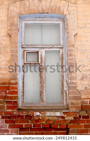 Weathered wooden window on brick wall. Old cracked wall with a window in Astrakhan, Russia. - stock photo