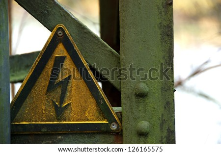 Weathered yellow electricity warning sign with back bold mounted onto metal - stock photo