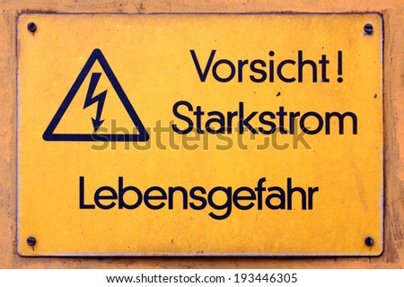 Weathered yellow German-language sign warns of high voltage (Starkstrom) at an industrial facility. - stock photo
