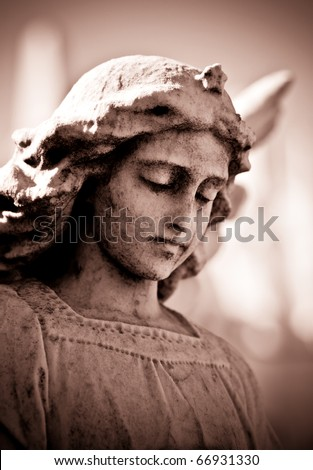 Weathered young angel in sepia tones - stock photo
