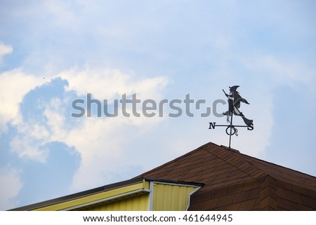 weathervane on the roof of the brown residential building on a background of blue sky with clouds
