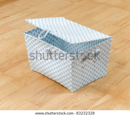 Weaved plastic basket with a lid and handle for storage stuff or laundry - stock photo