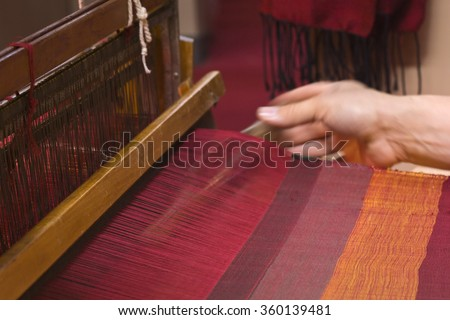 Weaver working on the old loom - stock photo