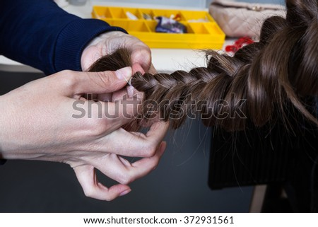weaving braids girl in a hairdressing salon - stock photo