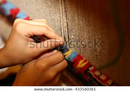 Weaving carpet  with traditional techniques on a loom. Wool yarns used as a warp and weft is crucial for this art.  - stock photo