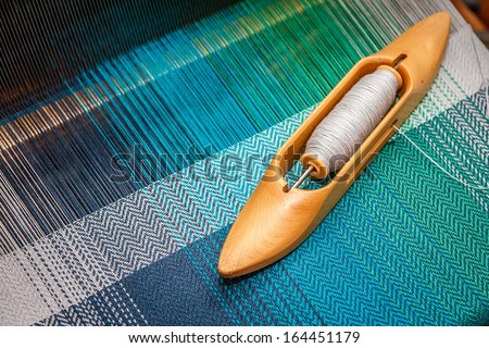 Weaving shuttle on the warp - stock photo
