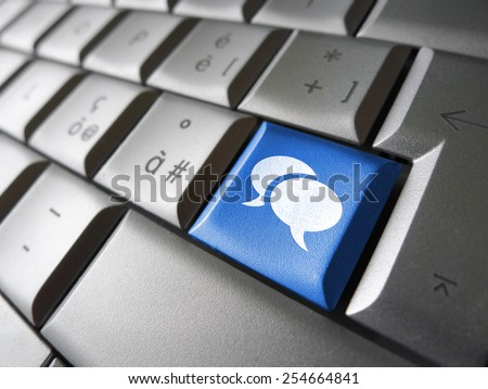 Web and social media concept with speech clouds icon and symbol on a blue laptop computer key for Internet and online business. - stock photo