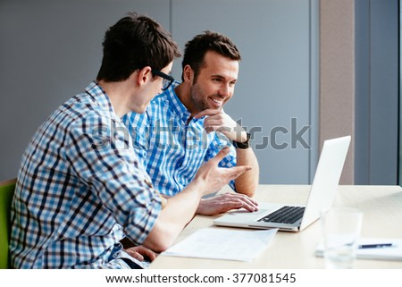 Web designers at office working with laptop - stock photo