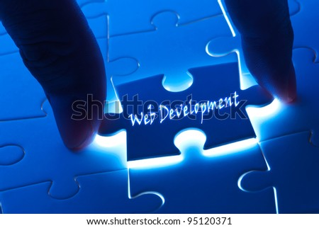 Web development on puzzle with back light - stock photo