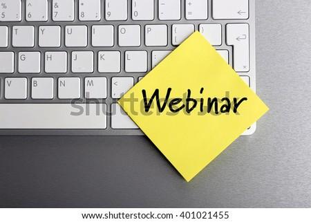 Webinar written on sticky note on laptop keyboard - stock photo