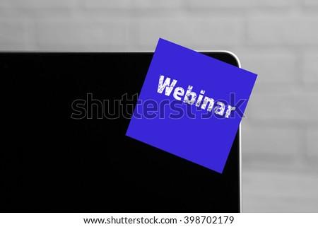 Webinar written on sticky note on laptop screen - stock photo