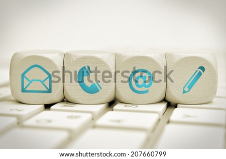 Website and Internet contact us page concept with blue icons on keyboard - stock photo