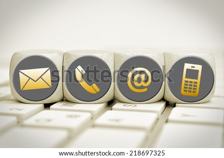 Website and Internet contact us page concept with icons on cubes on a keyboard - stock photo