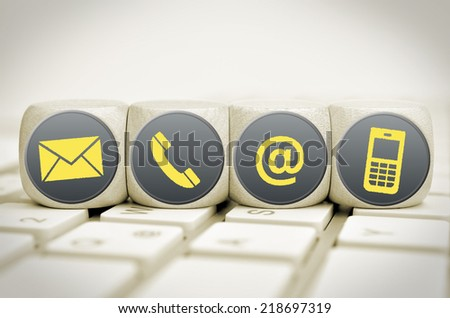 Website and Internet contact us page concept with yellow icons on cubes on a keyboard - stock photo