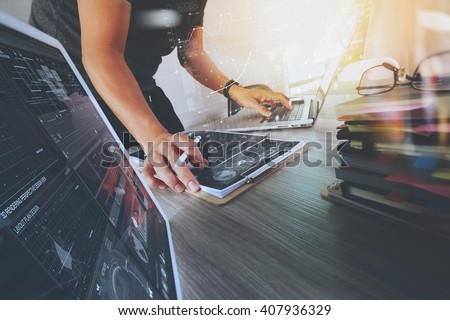 Website designer working digital tablet and computer laptop with smart phone and graphics design diagram and stack of books on wooden desk as concept