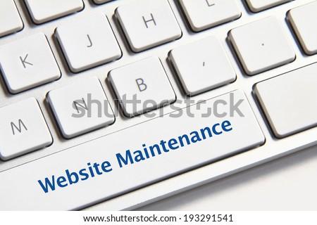 Website maintenance icon on white keyboard button - stock photo