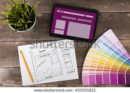 website wireframe sketch and digital tablet on wooden table - stock photo