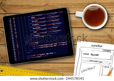 website wireframe sketch and programming code on digital tablet screen - stock photo