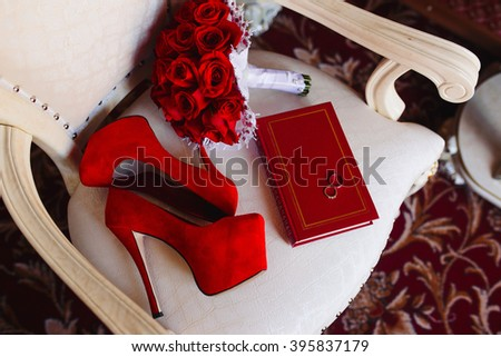 Wedding accessories bride red color on the chair. Red shoes. Brides bouquet of red roses. Two wedding rings on a book - stock photo