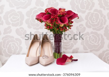 Wedding accessories: Bride's shoes, bouquet and red boutonniere from lily callas - stock photo