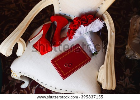 Wedding accessories the bride red. Red shoes. Brides bouquet of red roses. Two wedding rings on a book - stock photo